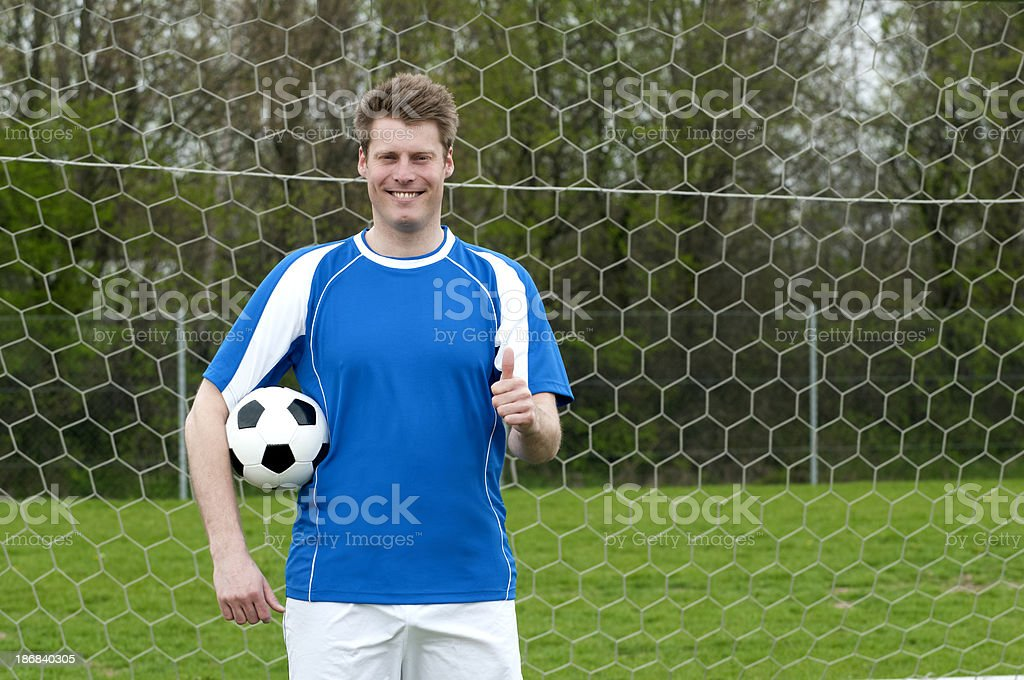 Happy soccer player shows a thumbs up royalty-free stock photo