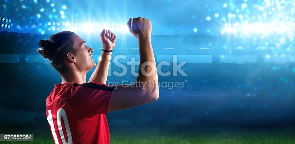 istock Happy soccer player with goal joy in the 3d imaginary stadium background 972557054