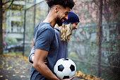 istock Happy soccer players with ball talking on field 901571932