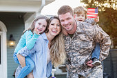 Excited mid adult Caucasian soldier is happy to be reunited with his young family.