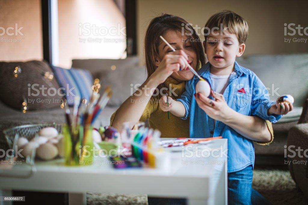 Happy son and mother preparing creative eggs stock photo
