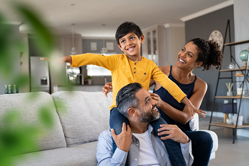 Cheerful indian son sitting on father shoulder playing at home with african mother. Playful little boy with stretched arms enjoying spending time with parents at home. Flying child enjoying playing with his ethnic family.