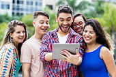 istock Happy spanish hipster student with tablet computer and group of cheering international students 1130075109