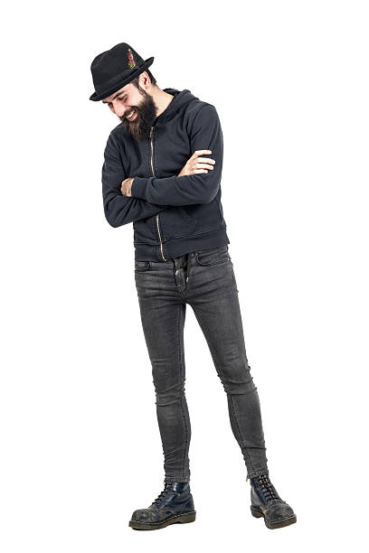Happy spontaneous laughing hipster with fedora hat looking down Happy spontaneous laughing hipster with fedora hat looking down. Full body length portrait isolated over white studio background men in tight jeans stock pictures, royalty-free photos & images