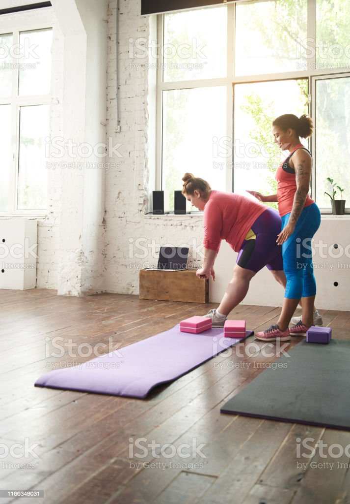 Smiling Afro American woman helping Caucasian fat lady doing exercises