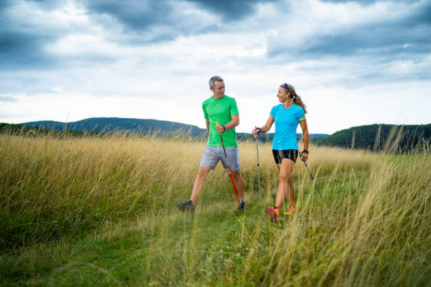 happy sportive couple looking smiling at each other nordic walking together active smiling middle aged couple doing nordic walking sport in grassland with shallow focus cloudy overcast sky dark clouds front view nordic walking stock pictures, royalty-free photos & images