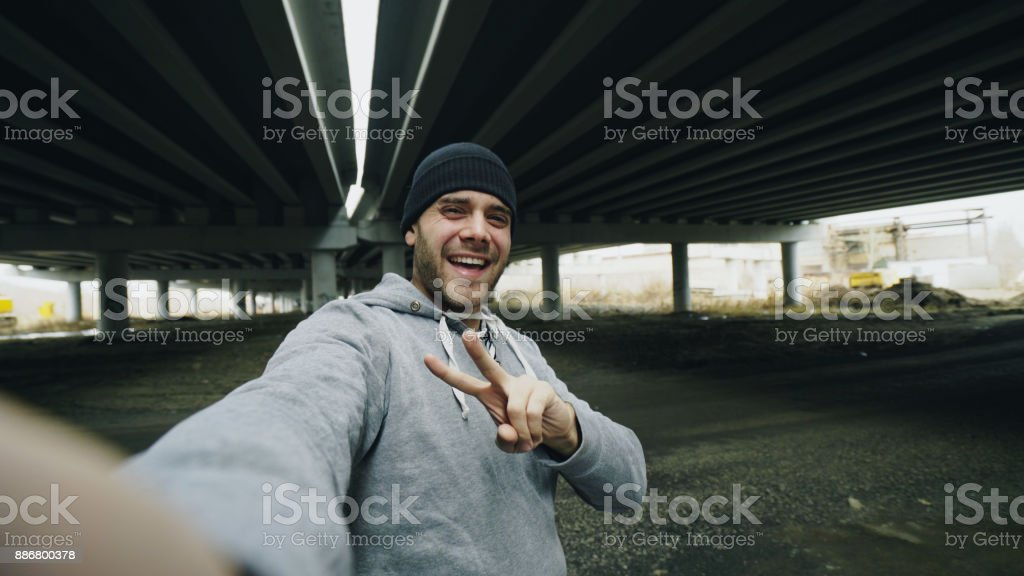 POV of Happy sportive man taking selfie portrait with smartphone after training in urban outdoors location in winter stock photo