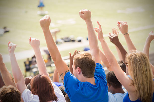 Happy sports fans cheering and celebrating in stadium stands stock photo