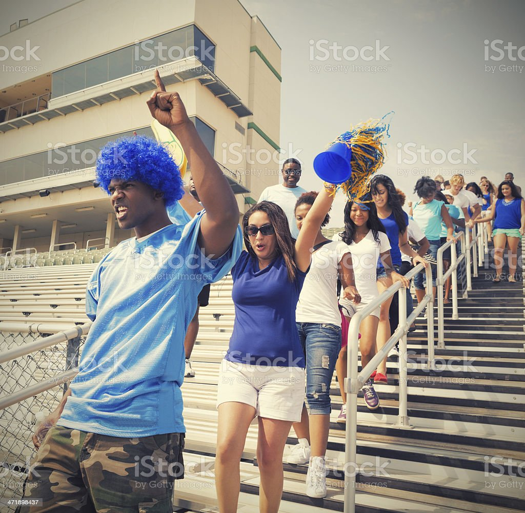 Happy sports fans exiting stadium after teams victory royalty-free stock photo