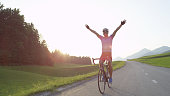 LENS FLARE: Happy sportsman riding his bicycle victoriously outstretching his arms while cruising through tranquil sunlit nature on gorgeous summer afternoon. Thrilled bicycle rider celebrates win.