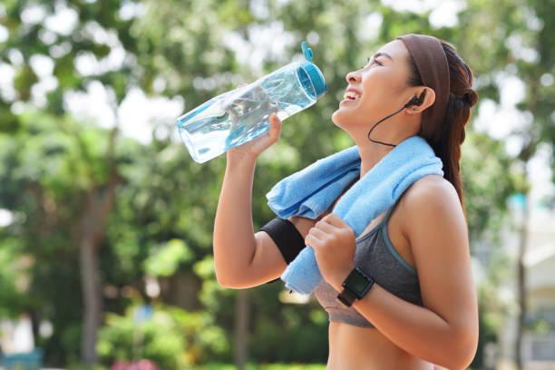glücklich sportlerin trinkwasser im park - armband water stock-fotos und bilder
