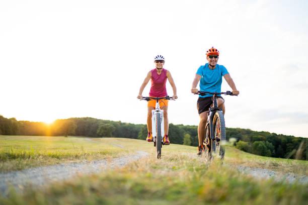 glückliche sportliches Paar Biken mit Mountainbikes bei Sonnenuntergang im Freien in der Natur – Foto