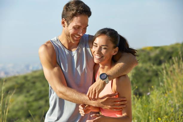 Fröhliches sportliches Paar umarmt im Sommer im Park – Foto