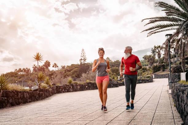 fröhliches sportliches paar im freien-fit freunde joggen und trainieren zusammen draußen-mensch, gesundheit, fitness und sport-lifestyle-konzept - laufende tattoos stock-fotos und bilder