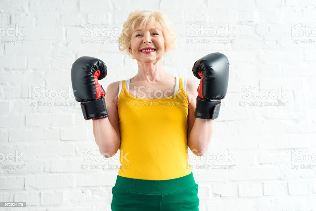 feliz mujer senior deportiva en guantes de boxeo sonriendo a cámara - foto de stock