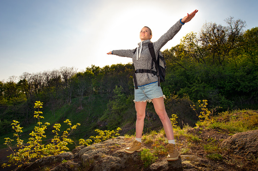 629376126 istock photo Happy sporty Traveler woman relaxing at sunrise beam, Female model breathing fresh air outdoors, Healthy active vacation concept 821787578