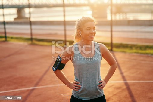 Happy sporty woman with hands on hips and earphones in ears standing on the court early in the morning.