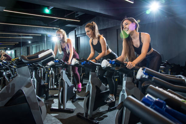 happy sporty women riding exercise bikes on cycling class in gym. - class стоковые фото и изображения