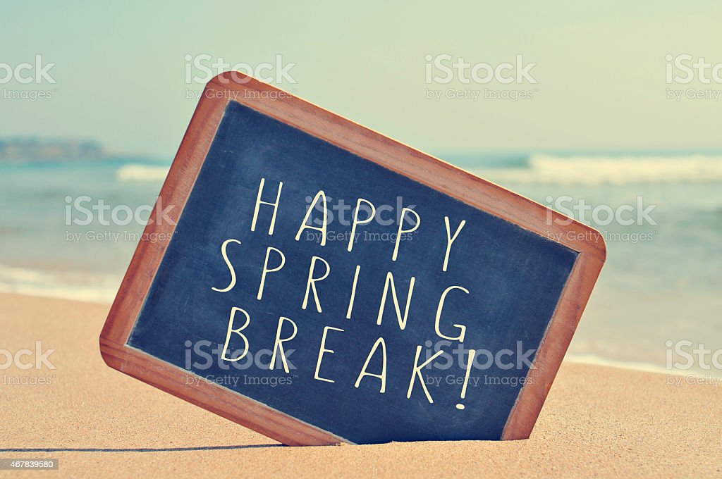 happy spring break in a blackboard on the beach stock photo