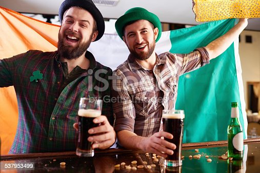 Two cheerful bearded men celebrating St Patrick's Day at pub
