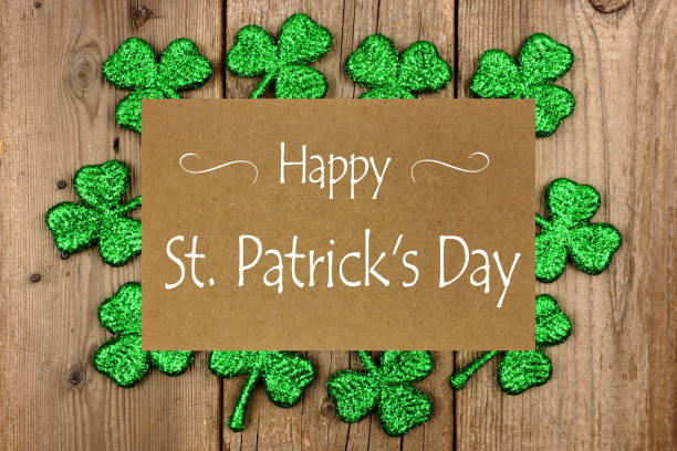 happy st patrick day greeting card with shiny shamrocks over rustic wood - happy st. patricks day stock photos and pictures