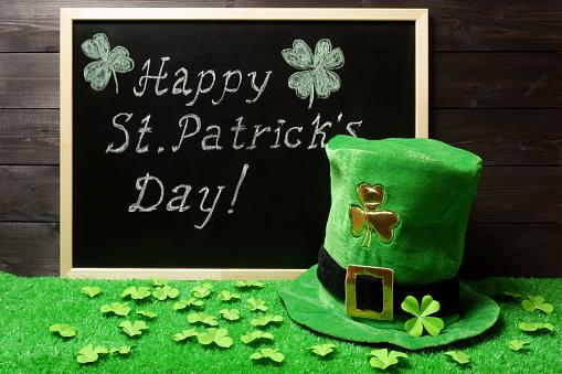 Happy St. Patricks Day chalk lettering on blackboard, green leprechaun hat and shamrock leaves on green grass. Dark wooden planks background. Saint Patricks Day banner, poster, invitation template