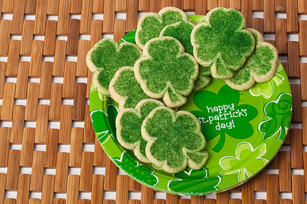 happy st. patrick's day cookies on a brown mat - st patricks day food stock photos and pictures