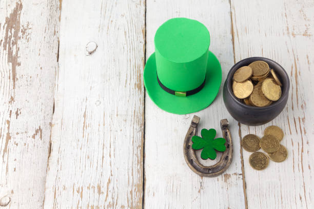 happy st patricks day leprechaun hat with gold coins and lucky charms on vintage style white wood background. top view - luck of the irish stock photos and pictures