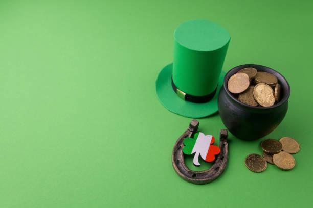 glücklich st. patricks day kobold hut mit goldmünzen und glücksbringer auf grünem hintergrund. ansicht von oben - st. patrick's day stock-fotos und bilder