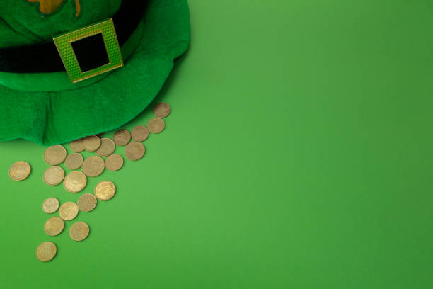 happy st patricks day leprechaun hat with gold coins on green background. top view - luck of the irish stock photos and pictures