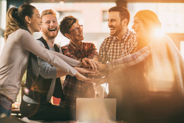 Happy start up team gathering hands in unity. stock photo