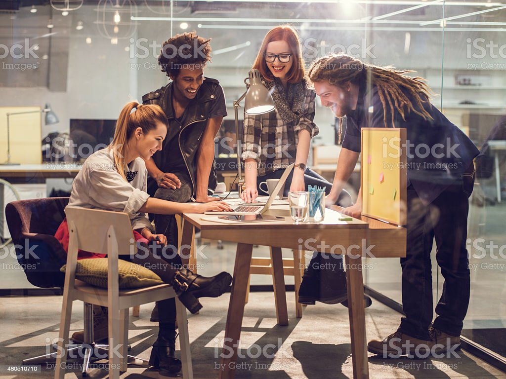 Happy start-up team using computer on meeting in office. stock photo
