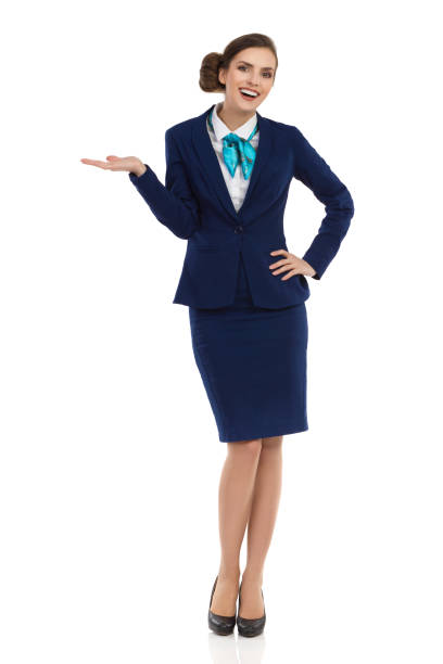 Happy Stewardess Is Presenting Smiling young businesswoman in blue formalwear and high heels is standing with hand raised and looking at camera. Front view. Full length studio shot isolated on white. air stewardess stock pictures, royalty-free photos & images