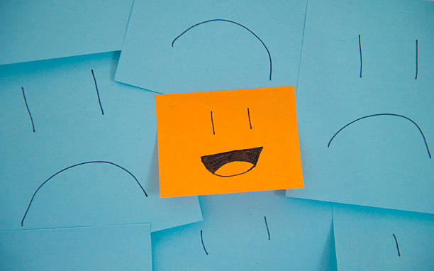 happy stick note amongst sad sticky notes. - frowning stock photos and pictures