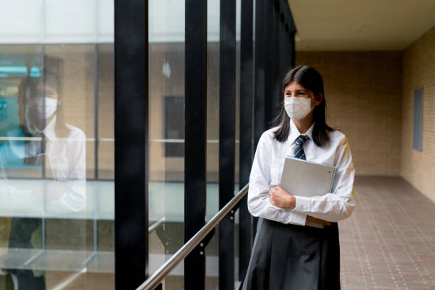 Happy student at the school wearing a facemask to avoid an infectious disease stock photo