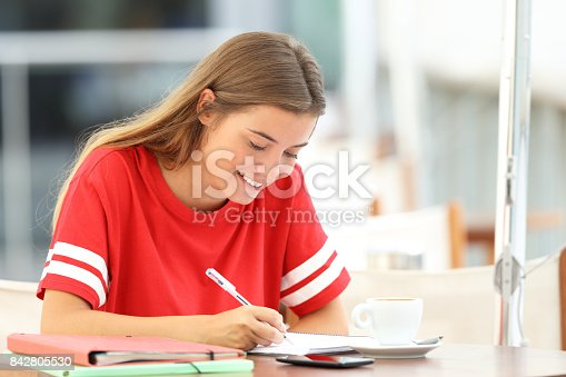 820495452 istock photo Happy student girl taking notes in a bar 842805530