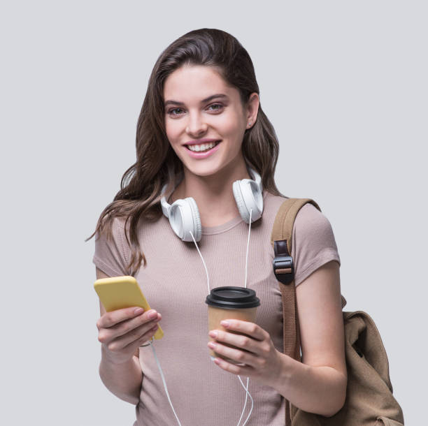 Happy student girl using smart phone and going on a travel stock photo