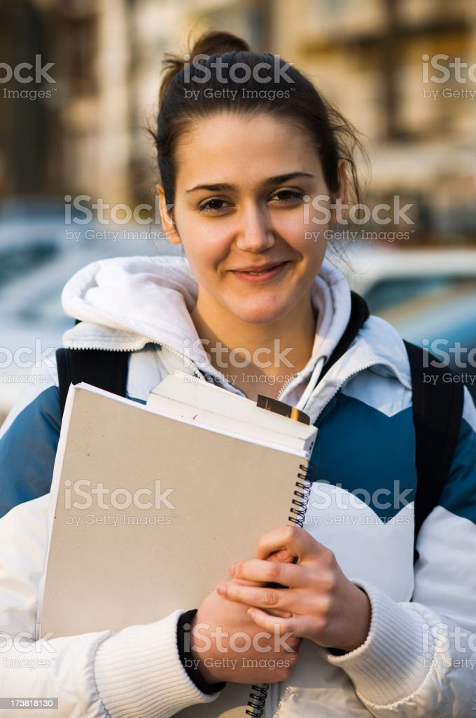 Happy student holding textbook in her hands royalty-free stock photo