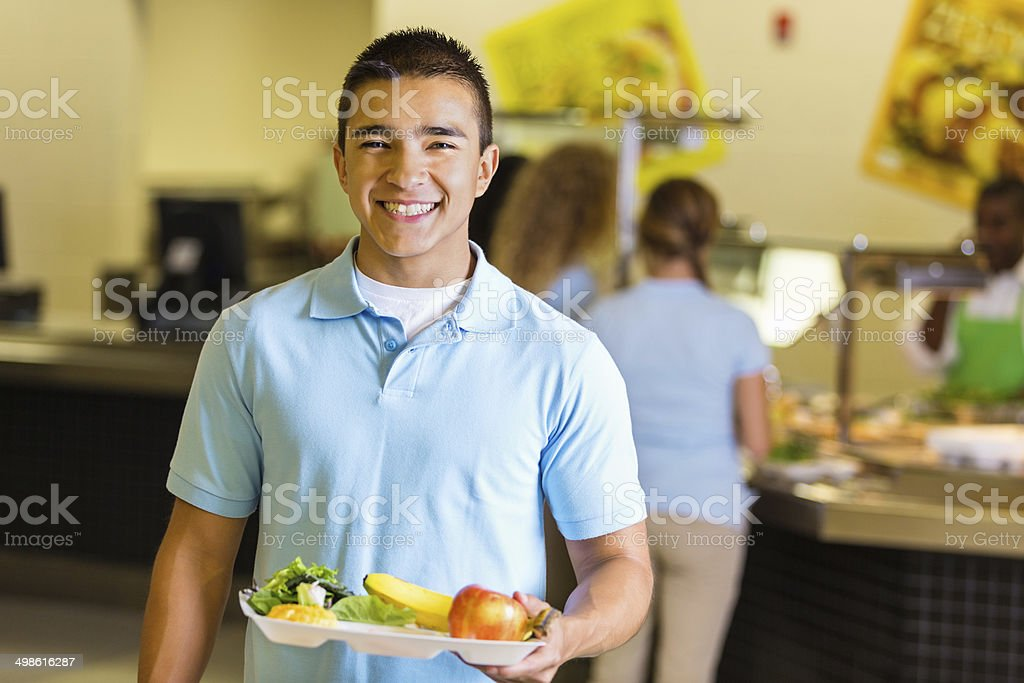 Happy student holding tray of healthy food in school lunchroom stock photo
