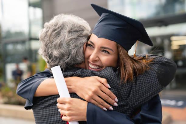 estudiante feliz abrazando a su padre y celebrando su graduación - graduación fotografías e imágenes de stock