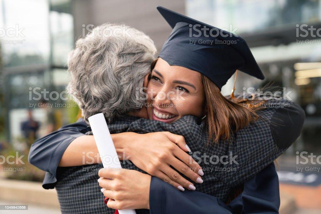 Glückliche Schüler ihr Vater umarmt und feiern ihren Abschluss – Foto