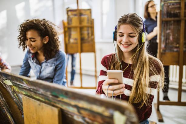 fröhliche schüler, die während eines unterrichts im kunstatelier musik hören. - high school bilder stock-fotos und bilder