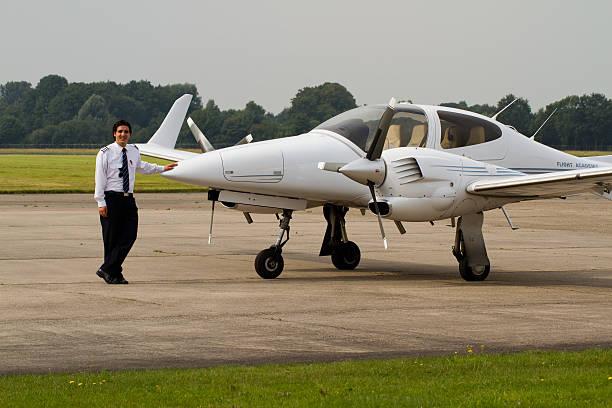 glückliche schüler pilot stehen neben einem flug school-flugzeug - flugschule stock-fotos und bilder