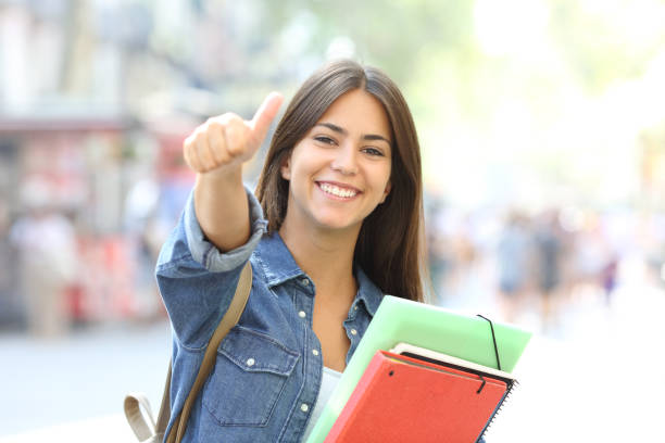 Happy student posing with thumbs up in the street Happy student posing with thumbs up looking at you in the street adult student stock pictures, royalty-free photos & images