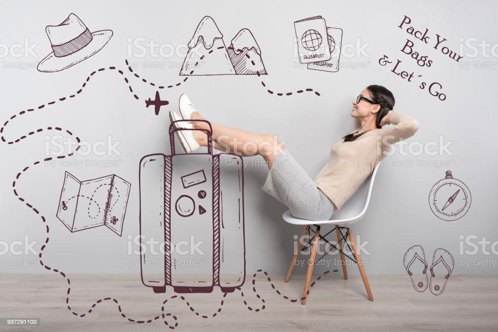 Heureux étudiant mettant ses pieds sur le sac et en attente pour le voyage - Photo