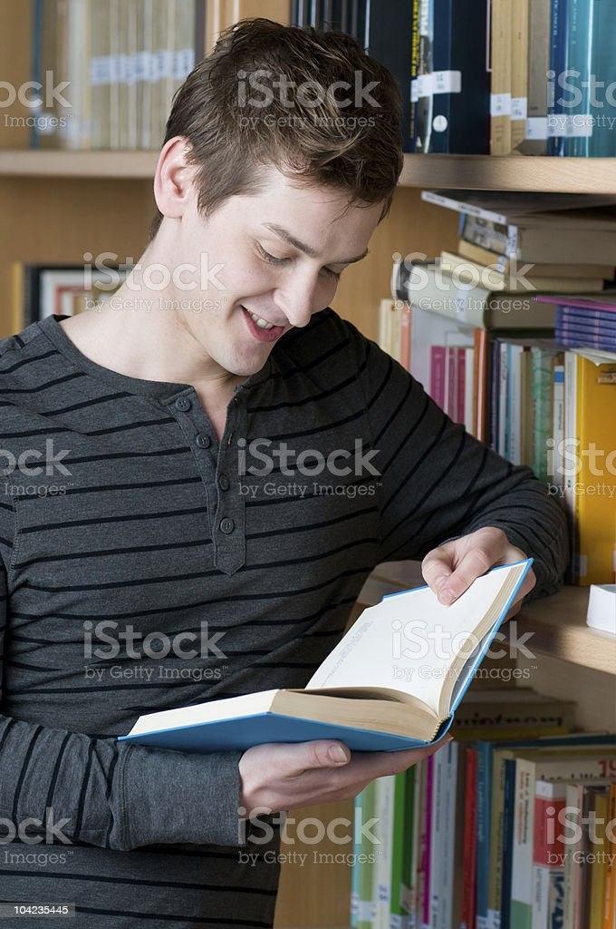 Happy student reading book in a library royalty-free stock photo