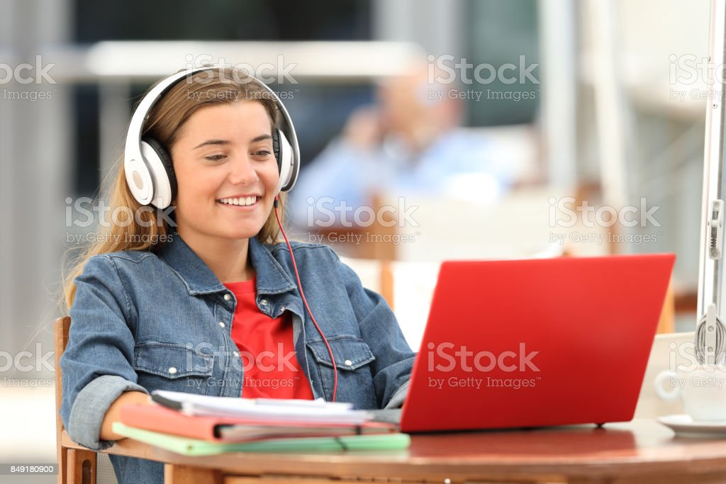Happy student relaxing watching on line content stock photo
