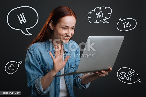 1003539592istockphoto Happy student smiling while having a video call with her parents 1003541742