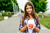 istock Happy student student girl holding a toy heart summer city. Free space text. Background of road green trees. Concept of love, blood and organ donation, give life. Save man Smile joy and tenderness. 1140662796