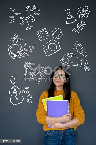 Happy student thinking about what to study as her major and looking at the options on a blackboard – education concepts